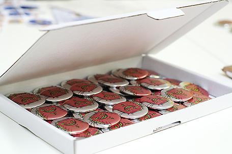 Versandkarton mit Metallicbuttons gefüllt