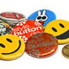 Haufen 32 mm Buttons im Vergleich zu 50 Cent Münze