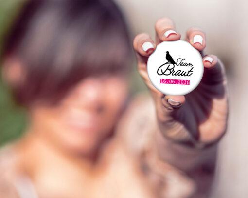 Freundin hält einen Button zum Junggesellinnenabschied in der Hand: Mod. #6 mit Taube