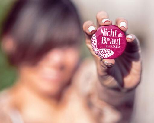 Frau mit JGA Button Nr. 8 in der Hand