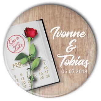 Hochzeitsbutton 46 mit Terminplaner und roter Rose auf Tisch: individualisiert
