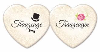 Zwei Buttons in Herzform mit Aufschrift Trauzeuge bzw. Trauzeugin