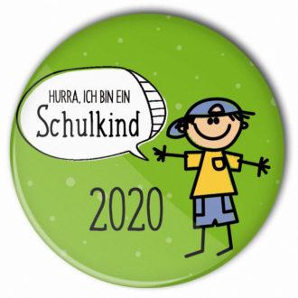 Schulanfang 2020: grüner Button Hurra ich bin ein Schulkind | Junge mit blauem Basecap und Hose, gelbes T-Shirt