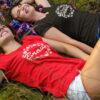 2 Frauen liegen zum JGA lachend im Gras und tragen JGA-Shirts T73