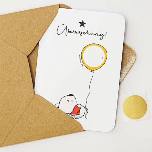 """Rubbelkarte mit einem Bär, der einen Luftballon (mit beschreibbarem Rubbelfeld) hält und der Überschrift """"Überraschung"""""""